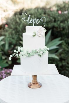 Garden inspiration is EVERYWHERE for floral wedding cakes!  We added touches of charcoal color speckling on the pale blue icing to give a robin's egg effect.  Sugar greenery & garden roses round out a soft effect on this otherwise modern layout.  Shot at The Inn at Rancho Santa Fe by https://www.cavinelizabeth.com/