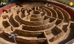 A circular straw bale #maze. Appears to be semi-permanent with a wall enclosing it.  Circular mazes are perhaps the closest form of maze design to the earlier labyrinth designs.