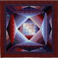 """Fragmentation"" -- dividing a patch into many smaller patches -- is a key design element of Borealis.  Jinny drafted her block, Inspiration Point, into a 60"" square. Then she divided each shape into smaller versions of the same shape to ""fragment"" the design. Careful color placement and shading creates a quilt with many glowing areas."