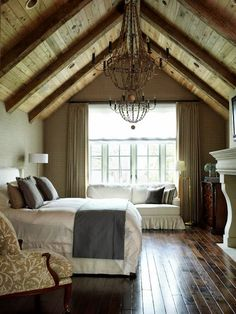 rustic bedroom…wood floors, white comforter and a chandelier….favs