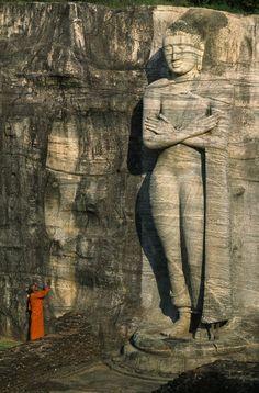Buddhist monk at the foot of a tall stone Buddha sculpture on a hill. Sri Lanka.
