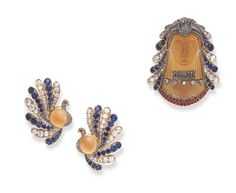 A RARE SET OF EGYPTIAN REVIVAL GEM-SET JEWELRY, BY TIFFANY & CO.  Comprising a pendant brooch, of carved citrine, depicting an Egyptian goddess, wearing an old mine, old European and rose-cut diamond and cushion-cut sapphire peacock headdress, further adorned by a rose-cut diamond and single-cut ruby choker and collar; and a pair of ear clips en suite, mounted in gold, pendant brooch circa 1910, ear clips circa 1945  Brooch signed Tiffany & Co. (2)