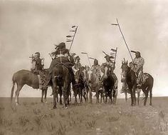 Here we present a dramatic image of Atsina Warriors. It was taken in 1908 by Edward S. Curtis.    The image shows Several Atsina warriors on horseback some with feathered staffs and one with a headdress.    We have created this collection of images primarily to serve as an easy to access educational tool. Contact curator@old-picture.com.    Image ID# 3CDEFECA
