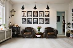 Gallery wall with matching frames and simple organized layout. Love the lights and chairs.