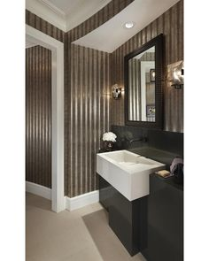 Look closely at the wall treatment...corrugated steel walls add a sculptural feel to this modern powder room.