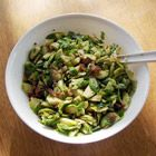 shredded brussel sprouts with pine nuts, green onions, and crumbled bacon