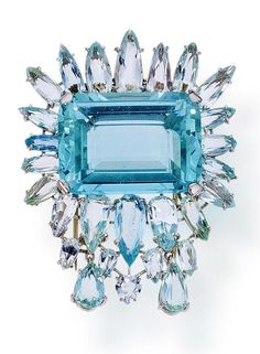 An aquamarine brooch centering a cut-cornered rectangular-cut aquamarine, surrounded by pear-shaped aquamarines, and suspending a flexible fringe; central aquamarine weighing approximately: 45.00 carats