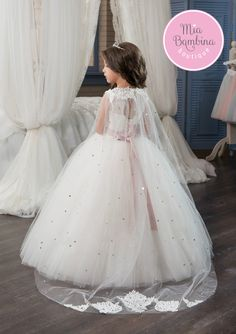 Enchant your guests with the Oxnard flower girl or First Communion dress. This lace and tulle gown features a Princess-style silhouette that is complemented with a floor-length multi-layered tulle skirt. The lace over satin bodice showcases a charming jewel neckline, a keyhole corset back, as well as sparkling sequins and rhinestones embroidered front and waistband. The detachable cape is adorned with an elegant spray of lace along with sparkling rhinestones throughout.
