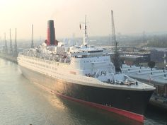 The elegant Queen Elizabeth 2 lies patiently, if incongruously, at anchor in an industrial setting wholly at odds with the iconic liner's glamour.