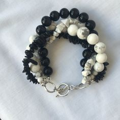 Black Jade and White Howlite Multi-Strand Beaded Bracelet with Toggle Clasp. Handcrafted one of a kind piece. * Black Jade (coated) 6 mm round. * Black Sheen Obsidian (natural) medium chip. * White Howlite (natural) medium chip. * White Howlite (natural) 6 mm, 10 mm, 12 mm round. * Closure: Antique Silver-Plated Pewter Toggle Clasp. * Total length from clasp to clasp is approx. 8.5.  *** Unless otherwise noted, all of the findings in the jewelry is plated. Plated findings have a brass core…