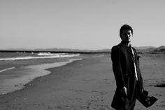目鼻立ちのくっきりした新郎。影と光を使い、さらにモノクロ写真にすることでよりクールに。風でなびくジャケットと打ち寄せる波がポイントの結婚写真です。徳島県小松海岸で洋装ロケーションウェディング。