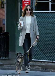 Back in business: Dakota Johnson revived herself with a cup of coffee as she walked her dog Zeppelin through New York on Sunday