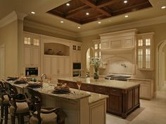Love the raised, stained wood ceiling in this otherwise white Kitchen, and love the way the island matches it...