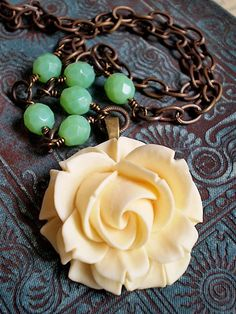 vintage style ivory resin rose focal with a carved vintage look to it. Focal is accented with Vintaj brass and vintage style apple green colored Czech glass.