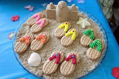 A tray of super cute nutter butter/frosting sandals! The shells and starfish were made using a shell mold found at Michaels! The sandcastles were made by packing brown sugar into small sand castle molds (found at Dollar Tree!) They were one of my favorite details! http://www.diddlesanddumplings.com/2013/03/hawaiian-party-desserts.html?m=1