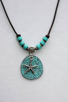Green patina Mykonos pendant with Tierra Cast antique silver plated starfish charm, hanging from silver plated bail, leather cord necklace with turquoise Mykonos ceramic bead accents. Necklace is approximately 19 inches long, pendant measures approximately 1 inch. See my other