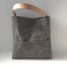 A casual, gray tote bag crafted from canvas that has been waxed with pure filtered beeswax and then sun-dried. Super durable, this waxed canvas bag will soften and become more creased and distressed with use; giving it that sought after well-worn, lived-in look!Our bucket tote has an easy-carry-shape and includes 5 slip pockets (2 outside and 3 inside) as well as a large interior zippered pocket. A double-wide, natural leather strap and nickel plated hardware complete the look.FREE Shipping…