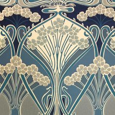 Ianthe Flower Wallpaper A timeless wallpaper design, originally created by well known French Art Nouveau designer, R. Beauclair in approximately 1900. 'Ianthe' is Greek for purple or violet flowers, suggesting that the flowers in the design may have originally been drawn from violets. It is shown here in shades of teal, indigo and steel blue on a cream ground.