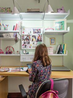 Sector de estudio del cuarto de una niña con una biblioteca modular regulable de metal blanco y una amplia mesa de trabajo en guatambú.