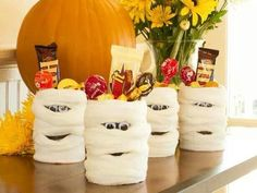 Mummy cans for Halloween candy. Made out of gauze or cheese cloth and tin cans spray painted black. Pull back fabric Insert eyes and make a mouth using a little glue. Add candy for festive party favors.