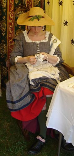 wool petticoat, a linen petticoat, a linen hand-hemmed apron, knitted stocks, and period reproduction shoes with pink grosgrain ribbon ties.    The hat is trimmed with pheasant and cockerel feathers, and has a beautiful hand made yellow rosette on the back where you can't see it.
