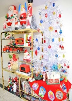 Milo Baughman etagere with a silver tinsel Christmas tree plus vintage blow molds.