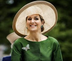 For this event, she repeated her slice brimmed picture hat in transparent wheat gold straw. It was this hat's first pairing with Máxima's emerald silk suit (she has worn it in the past with this pink ruched calot).