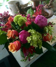 Large hurricane cylinder leaf lined with green hydrangea, cherry brandy roses, bright pink peony and red butterfly snaps.