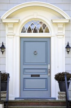 The front exterior of the house is painted white. It has a periwinkle blue door which features a metallic blue door knocker, door lock, and handle. The door also has a mail slot. It has a white door casing with an arched glass transom above. A pair of door lamps are  installed beside the front door. Two big black planters are placed right on top of the doorstep. The front steps are made of red bricks and have black steel handrails installed on either side.