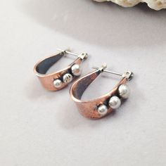 Rustic, yet refined, goes-with-everything earrings.Hand created from 20g copper and solid sterling silver balls. Lightly patina'd then polished. Hangs from a hinged sterling silver wire.Earring measures 5/8 long Ready to ship.These earrings are in...
