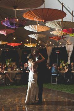 Para romper con los estereotipos coloca sombrillas de colores que adornen en techo del lugar de tu boda.