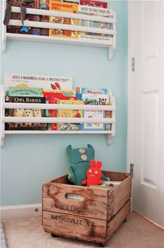 Great idea for small nursery - wall mounted book rack (place under/over a floating shelf at table height near reading chair)