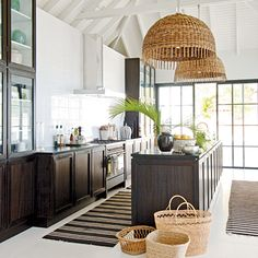 Dark wood, light walls, and natural elements, from the woven lighting to the handy baskets, make this coastal kitchen a breath of fresh air | Coastalliving.com