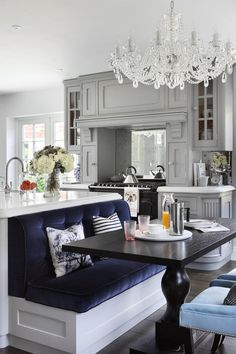 White cabinets, plush navy blue banquette, and a blingy chandelier makes a gorgeous kitchen.