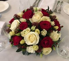 Wedding table centre posy of red and white roses, skimmia and hypericum berries