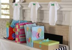 we could maybe hang that string of onesie's on the wall above the gift table...
