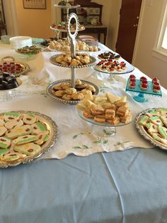 Vintage linens and tiered plate stands for finger sandwiches and desserts at a tea party.