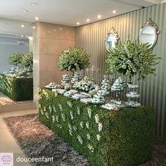 mesa de dulces con mantel de pasto arreglos florales redondos en floreros y cristalería, postres en blanco