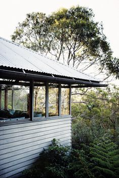 Ken Woolley Beach House Photograph of a corner of the house with large glass windows, timber cladding and corrugated tin roof. It is surrounded by native tree tops Timber Cladding, Exterior Cladding, Black Cladding, Corrugated Roofing, Corrugated Tin, Tin Roof House, Studio Shed, Blue Roof, Concrete Interiors
