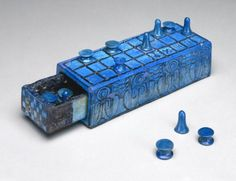 "Game, Egypt (Thebes), 1390-1353 BC, The Brooklyn Museum. ""This board and gaming pieces were used to play the game the Egyptians called senet, or ""passing."" Two players each used seven pieces to advance according to the roll of stick-like dice, jump over the other player's pieces, and finally remove all pieces from the board. The first player to remove all pieces won rebirth into the afterlife. This game was played for over 3000 years, and its board and pieces were often included in the…"