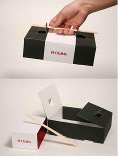 Una caja de sushi para llevar que usa los palillos como asa.