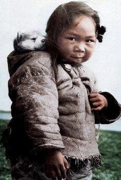 Husky puppy sleeping in Inuit girl's hood! Too cute.