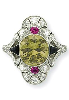 AN ART DECO COLORED DIAMOND, DIAMOND, RUBY AND ONYX RING Set with a circular-cut fancy light to fancy brownish greenish yellow diamond, with cabochon ruby and onyx detail, to the circular and single-cut diamond lozenge-shaped surround, mounted in platinum, circa 1920