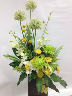 a beautiful asymmetrical arrangement in green, white and yellow created by one of our designers
