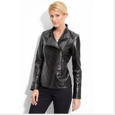 """Black leather motorcycle jacket by John Carlisle Bought this a couple of years ago from Nordstrom, wore it a couple of times. Supple leather, back is beautifully stitched so it follows the contours of your body, zip pockets and details at wrists, front asymmetrical zipper, fully lined. Arms are too long for me (5'-3"""" with shorter arms). There are two slight smudge marks at both shoulders so please check out the pictures. I never noticed this until I inspected it for this listing, might have…"""