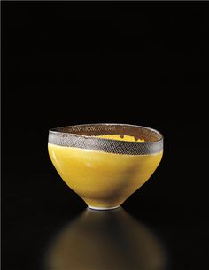LUCIE RIE, Oval bowl. 1976, Porcelain, yellow and manganese glazes with sgraffito band. 9.5 cm (3 3/4 in) high, 15.2 cm (5 7/8 in) wide