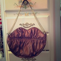 """Stunning sparkling purple lip shaped purse Purse is about 14"""" long, lip-shaped, and is a beautiful purple/gold color. It has a small and large compartment on the inside and a zipper compartment. The handle has two gold adjustable chains on each side and at the top is a soft purple/gold handle the matches the color of the purse. Never been used and no visible flaws. Selena gomez Bags Shoulder Bags"""