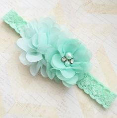 This Mint laced headband is perfect for any occasion! It is pairs with two chiffon flowers and embellished with rhinestone and pearl center.  Perfect as a baby shower gift, newborn baby,flower girl or everyday wear!  **** also available in many other colors***