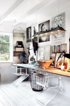 I'm wild about pretty much everything here:  the art, the uniquely-shaped clear acrylic chairs, the rustic wire basket... love this space!