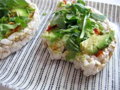 simple snack: avocado spread across rice cakes with a nice dose of Sriracha sauce and topped with some diced arugula